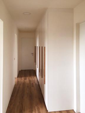 bílý byt a chodba s vestavěnými skříněmi