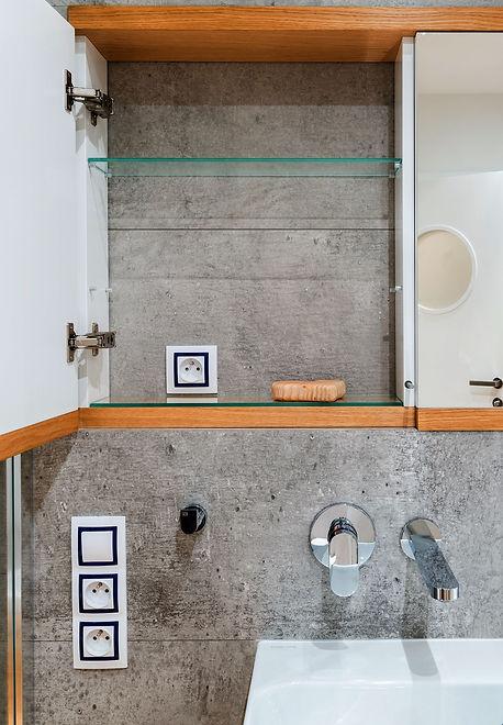 betonová koupelna a zrcadlová skříňka na