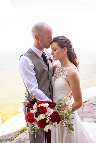 A man kissing his bride on the forehead as she shows her flowers to the camera