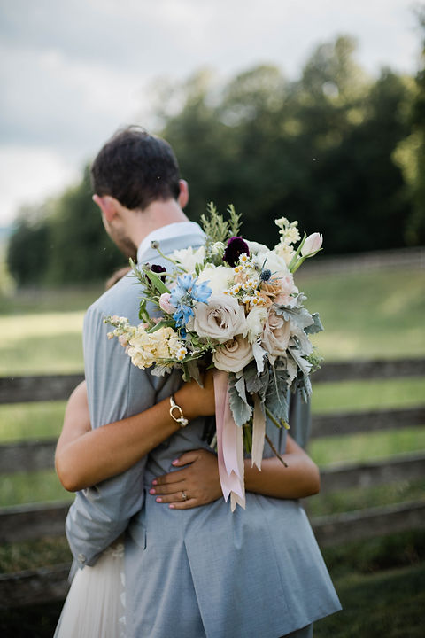 Bride's bouquet on the grooms back as they hug in celebration of their marriage