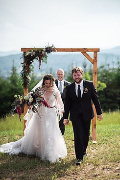Bride and groom smiling as they walk back down the aisle after they are married. The bride has a large bouquet in her hand with a greenery arbor behind them.