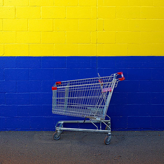 Shopping trolley against a blue and yellow wall