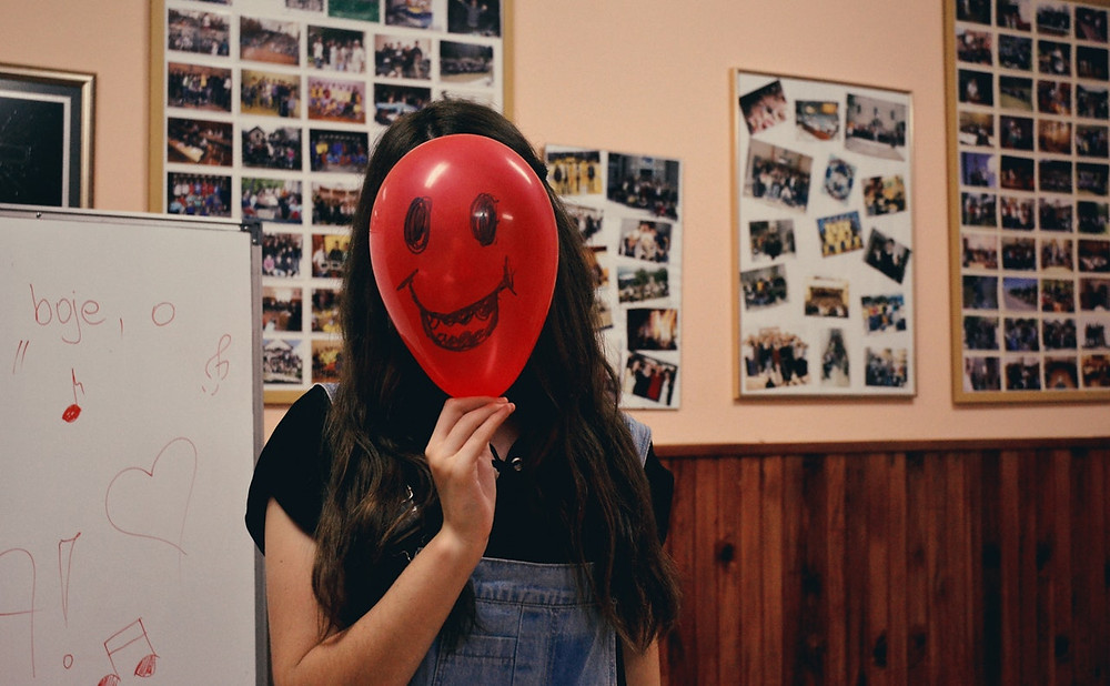 Woman with smiling balloon in front of her face in a classroom