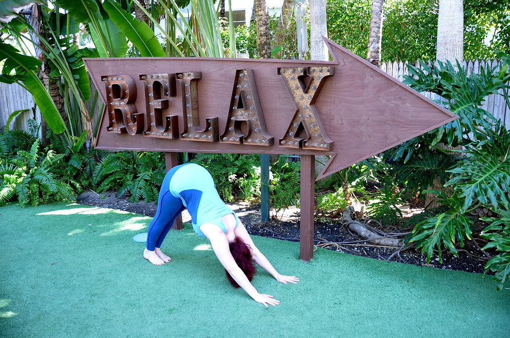 Claudia Brown doing a yoga downward dog in front of a relax sign