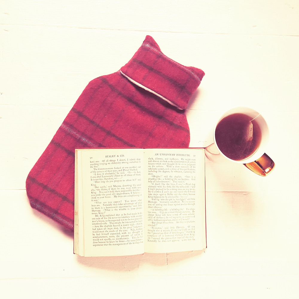 Hot water bottle, tea and book for seasonal self care
