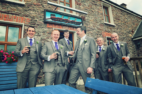 Groom and groomsmen having a pint by Clearys Photography.