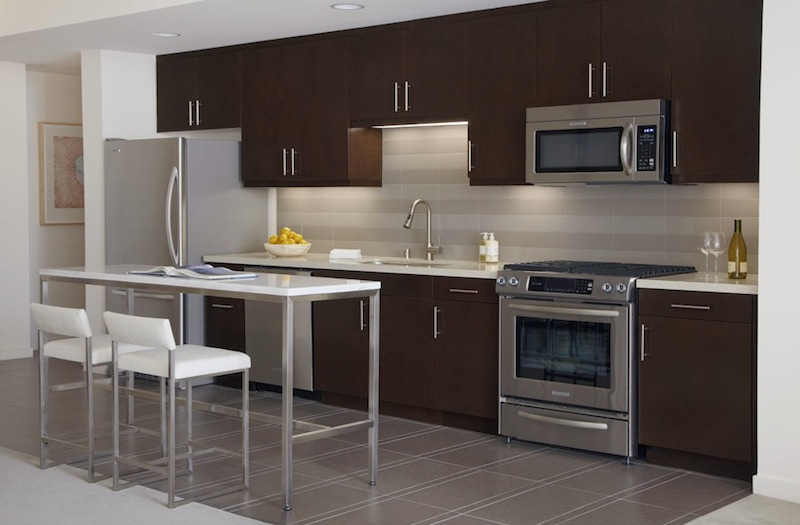 The Avenue kitchen brown cabinets and white walls