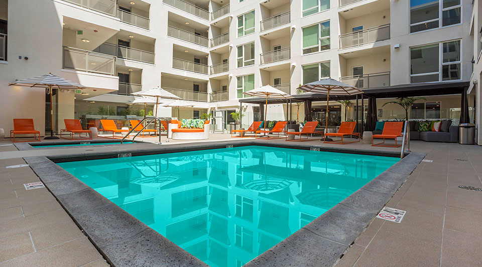 Onyx Apartments outdoor swimming pool with cabanas and reclining chairs