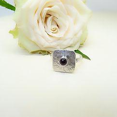 Zilveren ring met hamerslag motief en granaat steen