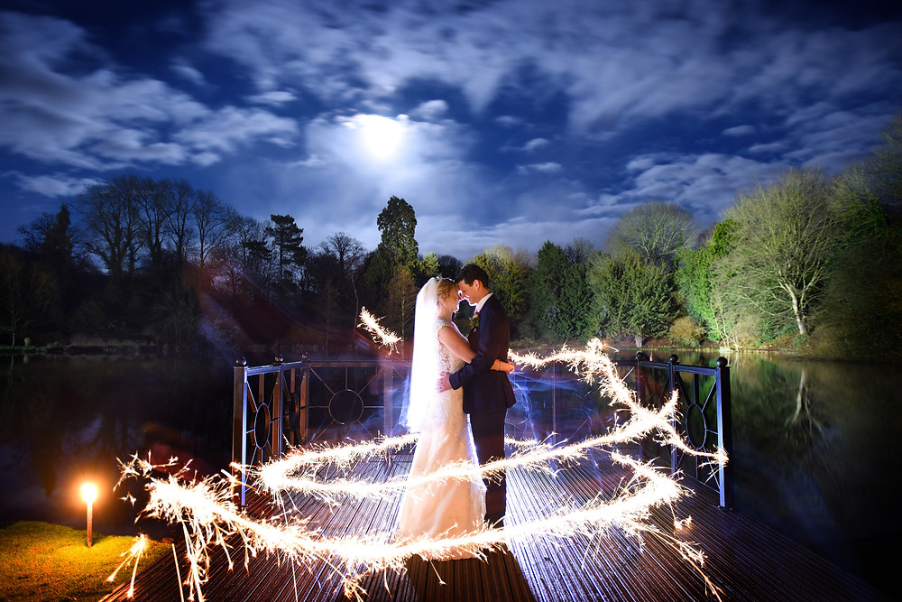 Newly weds surrounded by sparklers in night-time shot