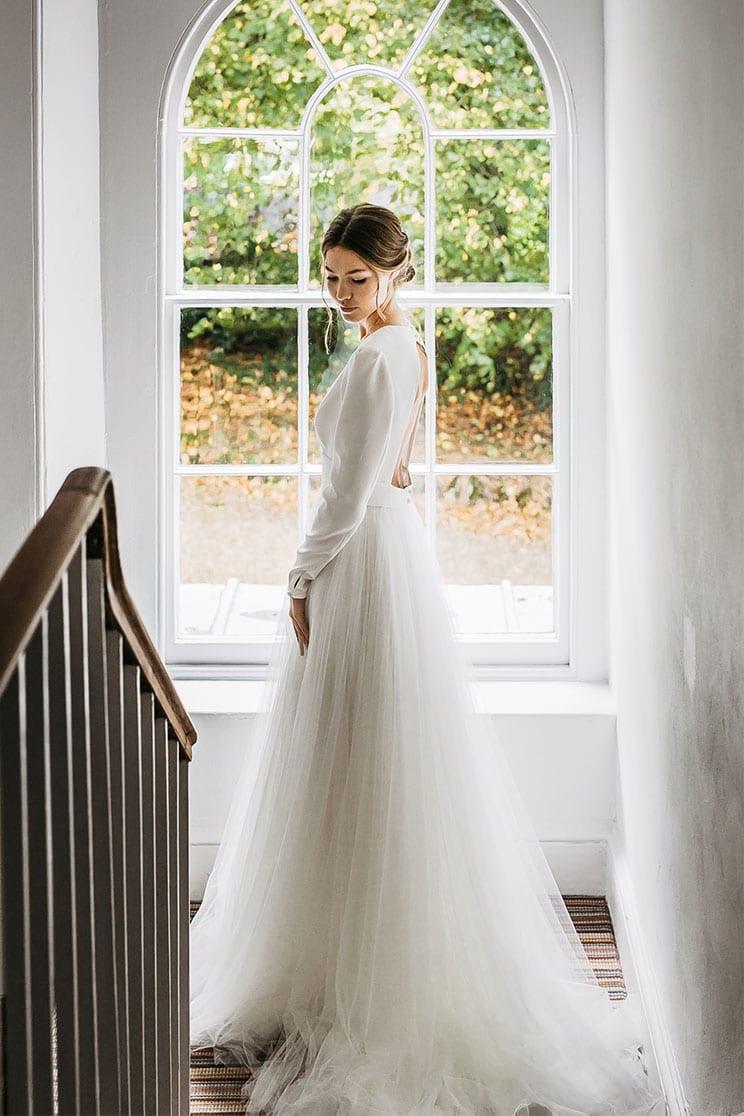 Bride stands in front of Georgian window