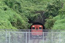 生野トンネルから顔を出す列車