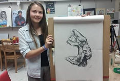 student smiling and holding figure drawing