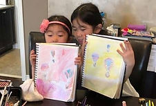 two children holding their drawings of hot air balloons