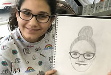 young student holding drawing of self portrait