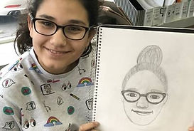 student-showing-drawing-of-self-portrait