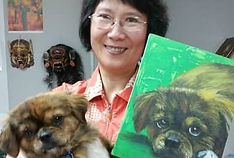 art student holding her dog and a painting of her dog