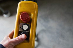 stock-photo-male-hand-push-remote-control-switch-for-overhead-crane-in-the-factory-close-u