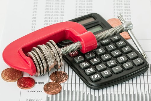 coins in clamp with calculator and budget sheet