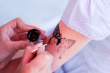 girl draws a temporary tattoo on his sho