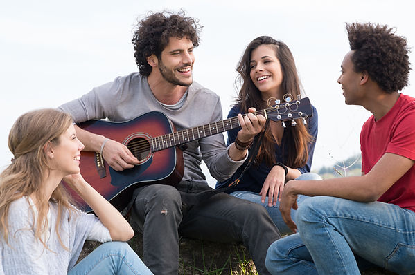 Group Of Happy Friends With Guitar Havin