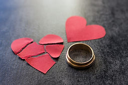 Wedding rings and broken red  heart. Black background. The concept of divorce, parting, in