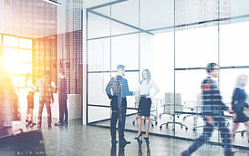 Busy office interior. Group of colleagues are standing near reception counter. Pair of peo