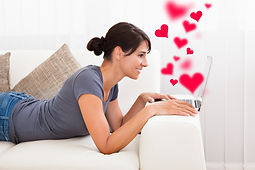 Side view of young woman dating on laptop with heart shapes at home.jpg