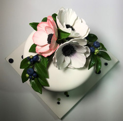 one tier cake with sugar flowers and ber