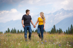 Couple walking hand in hand through a field.