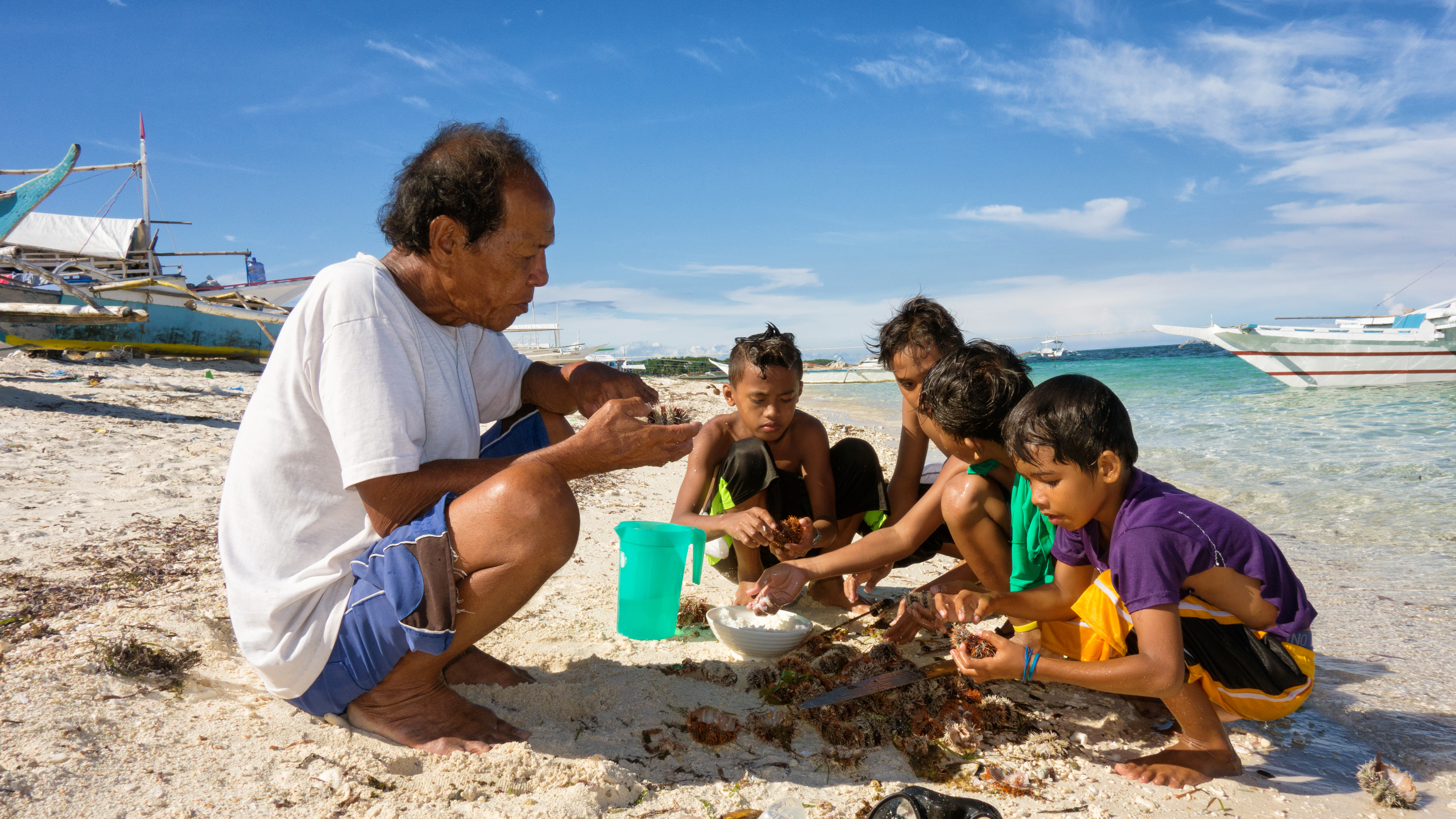 A man and four boys shucking oysters on a shoreline in the Philippines