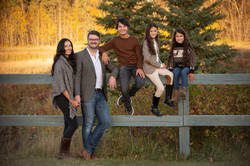 Family of five standing in front of a wooden fence