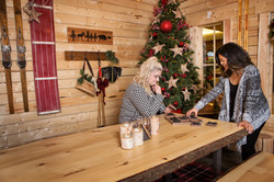 Two women playing a game in a Christmas cottage setting