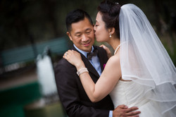 A bride kissing her groom on the cheek
