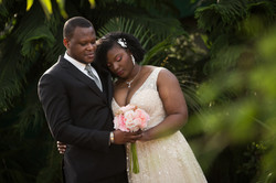 A bride and groom pose together with their eyes closed