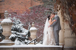 A bride and groom kissing in front of Convocation Hall