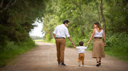 Family of three walking down a pathway.