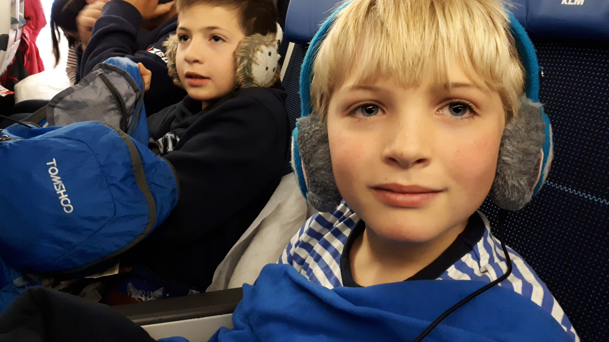 The little travel experts, tucked in and headphones 30 seconds after boarding the KLM Boeing 777
