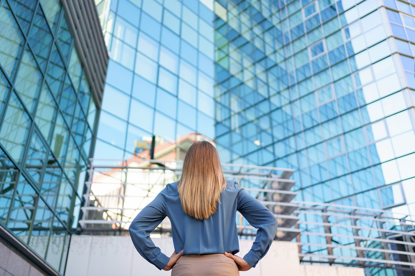 back-view-woman-looking-business-buildin