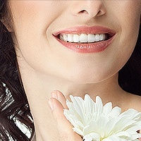 A Woman Smiling Holding a Flower