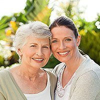 Young Woman and Elderly Woman Huggin and Smiling