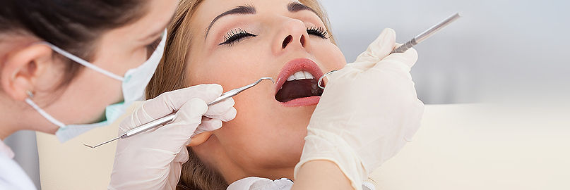 Woman With Mouth Open While Dental Professional Looks Inside