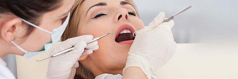 Woman with Mouth Open While Dentist Looks Inside