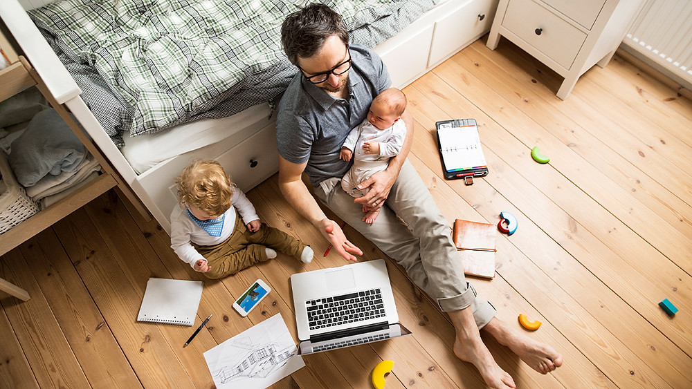 Work from home parent. Children and parent both using digital devices - computers, smartphones