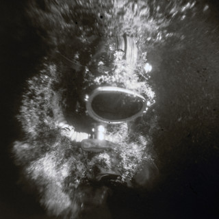 The picture was taken under water by a film camera of the size 18 by 24 cm. Monocle. Without a shutter. X-ray film. Flash Ikelite DS51. Model is wearing soviet diving dry suite УКГ2.