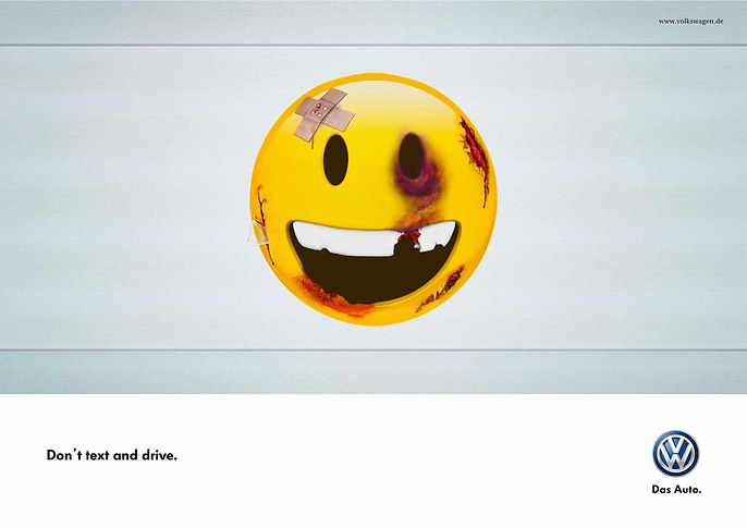 Volkswagen ad has a happy face emoji that is bruised and bleeding to show damage from a car crash.