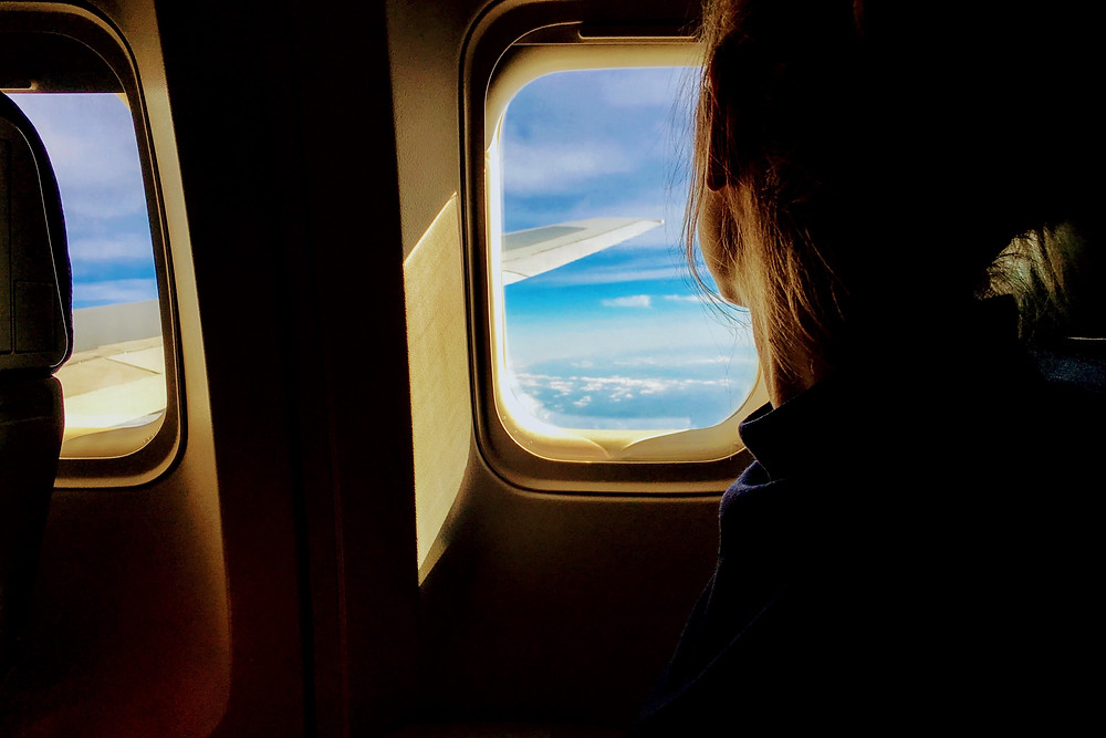Lady with fear of flying looking out of window in article by Harley Street Consulting