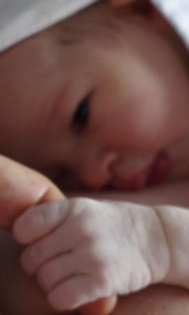 Newborn baby clasping mum's finger