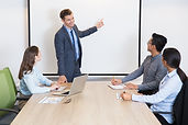happy-business-coach-consulting-team-in-boardroom.jpg