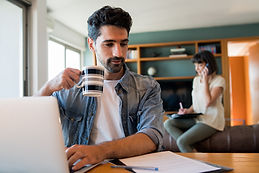 portrait-of-young-man-working-with-a-laptop-from-home-while-woman-talking-on-phone.jpg